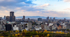 Osaka cityscape with overcast sky. Osaka city skyline with a park and river  in the foreground and mountains in the background.  A plane can be seen flying in Stock Photos