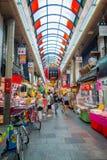 OSAKA, JAPÃO - 18 DE JULHO DE 2017: Povos não identificados que andam no mercado de preços do marisco da compra e da visita de Os Fotografia de Stock