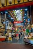 OSAKA, JAPÃO - 18 DE JULHO DE 2017: Povos não identificados que andam no mercado de preços do marisco da compra e da visita de Os Imagem de Stock