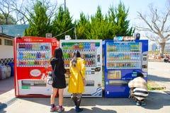 Osaka, Japão - 27 de março de 2015: Os turistas são máquina de moeda da bebida do uso no castelo de Osaka imagem de stock royalty free