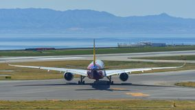 Passenger airplanes taxiing on runway. Osaka, Japan - Apr 19, 2019. Asiana Airlines HL7578 Airbus A350-900 taxiing on runway of Kansai Airport KIX. The airport royalty free stock photos