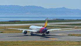 Passenger airplanes taxiing on runway. Osaka, Japan - Apr 19, 2019. Asiana Airlines HL7578 Airbus A350-900 taxiing on runway of Kansai Airport KIX. The airport royalty free stock photography