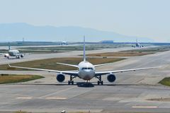 Passenger airplanes taxiing on runway. Osaka, Japan - Apr 19, 2019. Passenger airplanes taxiing on runway of Kansai Airport KIX. The airport located on an royalty free stock image