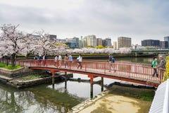 OSAKA JAPAN - April 6, 2016: Folket korsar röd fot- brid Royaltyfri Foto