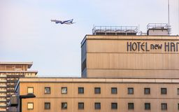 Façade of the hotel and a plane flying over it. Travel around Japan. 2013.01.05, Osaka, Japan. Façade of the hotel and a plane flying over it. Travel stock photography