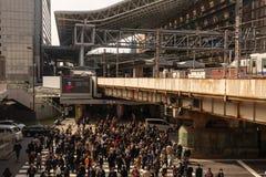 Osaka, Japan - February 27, 2019: Mass of people in crosswalk entering busy Osaka Station on sunny day stock photo