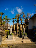 OSAKA, JAPAN - JULY 02, 2017: Beautiful garden with stoned structures and some palms tree behind in a sunny blue sky in Stock Photo