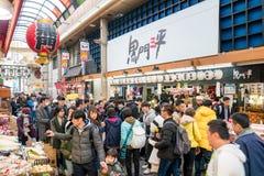 Osaka, Japan - 3 Mar 2018; Japanese local people, tourists and travelers walking and eating at Kuromon Ichiba Market fish market