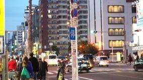 Osaka Japan - mars 2015 - folk som går i afton längs gatan i Osaka lager videofilmer