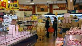 OSAKA JAPAN - mars 2015: Folk som går och shoppar i supermarket i japansk lokal fiskmarknad arkivfilmer