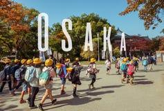 OSAKA JAPAN, MARS 12, 2015: Japanska unga elementära studenter Arkivfoto
