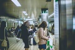 OSAKA, JAPAN - 10. NOVEMBER 2015: Osaka Stations-U-Bahn, die Leute zeigt, warten auf einen Zug und benutzen Smartphone Osaka, Jap Lizenzfreie Stockfotos