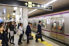 Osaka Metro station. OSAKA, JAPAN - NOVEMBER 22, 2016: People board a subway train in Osaka Metro, Japan. Osaka Metro has 133 stations and carries more than 2 royalty free stock photography
