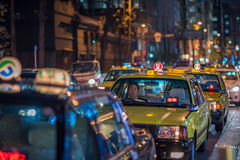 OSAKA, JAPAN - November, 17, 2014: Taxi cabs in the night street. OSAKA, JAPAN - November, 17, 2014: Taxi cabs in the night scene of Osaka Royalty Free Stock Photography