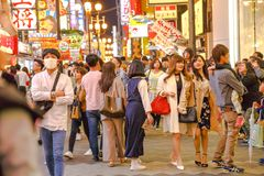 Osaka japanese people. Osaka, Japan - April 29, 2017: Japanese elegant people walking and shopping at night in Dotonbori district of Osaka, Japan. Night urban Stock Images