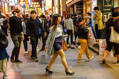 Osaka japanese woman. Osaka, Japan - April 29, 2017: Japanese woman walking at night in Dotonbori area of Osaka, Namba District, important tourist destinations Royalty Free Stock Images