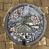 Osaka, Japonia: ściekowa nakrętki, manhole pokrywa/ląg/, Japoński język znaczymy Osaka obraz royalty free