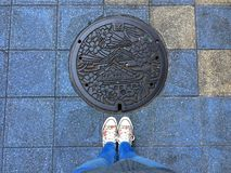 Female legs standing in front of a decorated Manhole in Osaka stock photo