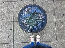 Female legs standing in front of a decorated Manhole in Osaka stock photography