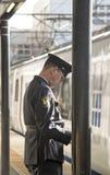 Osaka - 2010: Seitenansicht eines japanischen Offiziers an einem Bahnhof stockbild