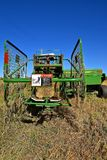 John Deere bale thrower parked in a field. OSAKIS, MINNESOTA , September 8, 2017: The bale thrower and cage parked in the stubble of a wheat field are products Royalty Free Stock Photos