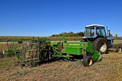 John Deere bale thrower parked in a field. OSAKIS, MINNESOTA , September 8, 2017: The bale thrower and cage parked in the stubble of a wheat field are products Stock Image