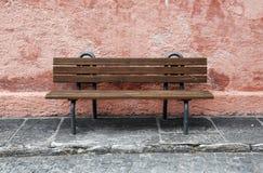 Osamotniona ławka przed pastle ścianą zdjęcie royalty free