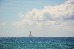 Osamotniona żaglówka w morzu na horyzoncie, połysku i promieniowaniu woda, Fotografia Royalty Free