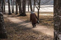 Osamotniona choroba zginająca kobieta chodzi wzdłuż parkowej alei zdjęcie royalty free