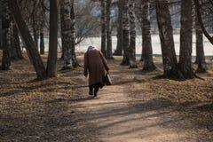 Osamotniona choroba zginająca kobieta chodzi wzdłuż parkowej alei fotografia stock