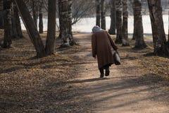 Osamotniona choroba zginająca kobieta chodzi wzdłuż parkowej alei zdjęcie stock