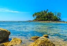 Osamotniona daleka wyspa z skały drzewem i plażą gdy woda morska Obraz Royalty Free