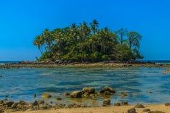 Osamotniona daleka wyspa z skały drzewem i plażą gdy woda morska Zdjęcie Royalty Free