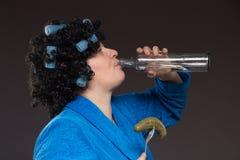 Osamotniona dojrzała gruba kobieta alkoholicznych napojów ajerówka od szkieł i fotografia stock