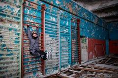 Osamotniona dzieciak dziewczyna w zaniechanej starej dziecko szkole, starawe ściany z krakingowych farb błękitnej zieleni żółtymi obraz stock