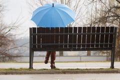 Osamotniona dziewczyna jest usytuowanym na ławce z błękitnym parasolem Fotografia Stock