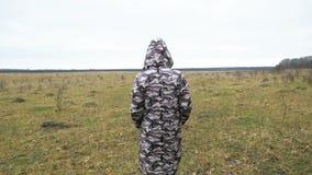 Osamotniona kobieta w długiej kamuflaż kurtce chodzi wzdłuż wielkiego pola Spacer w standardu miejscu zdjęcie wideo