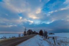 Osamotniona zimy droga która iść termin Wokoło śniegu bardzo piękne chmury przy zmierzchem Obrazy Royalty Free