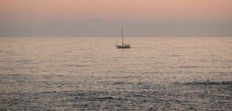 Osamotniony żeglowanie jacht na oceanie przy półmrokiem fotografia royalty free