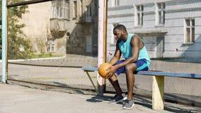 Osamotniony amerykanina sportowa obsiadanie na ławki i mienia piłce, depresja obraz stock