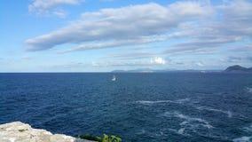 Osamotniony biały żagiel w błękitnym morzu Zdjęcia Royalty Free