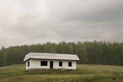 Osamotniony biały zapominający budynek na zielonej górze Głębokiego zmroku popielaty niebo z mnóstwo chmurami Las daleki krajobra zdjęcia stock