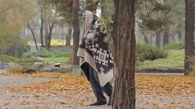 Osamotniony biedny człowiek utyka w parku, dziwaczny mężczyzna zakrywający z blanked potrzebami pomaga zdjęcie wideo