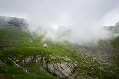 Osamotniony dom odizolowywający w zielonych pięknych skalistych łąkowych pobliskich wspaniałych trawiastych górach zakrywać w mgl Zdjęcia Royalty Free