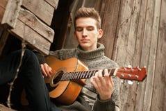 Osamotniony gitarzysta bawić się gitarą w przegranej wiosce Obrazy Stock