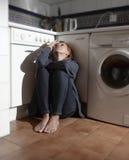 Osamotniony i chory kobiety obsiadanie na kuchennej podłoga w zdjęcia royalty free