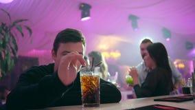 Osamotniony i przygnębiony facet pije alkoholu koktajl za prętowym kontuarem przy klubem na tle światła zbiory wideo