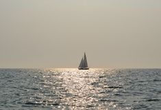 Osamotniony jacht w rozjarzonym morzu obrazy stock