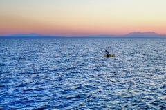 Osamotniony mężczyzna w rząd łodzi na morzu przy zmierzchem Obraz Royalty Free