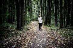 Osamotniony młody męski modniś w przypadkowych spacerach w jesień ciemnym markotnym lesie z spadać liśćmi zdjęcie royalty free